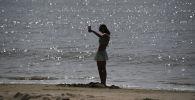 Девушка делает селфи на китайского островеа Хайнань. Архивное фото