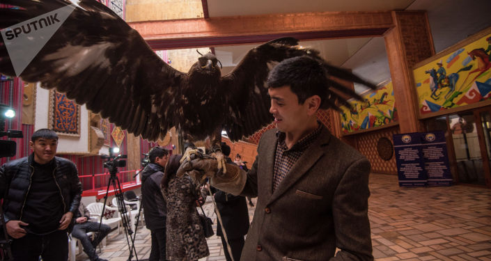 Мужчина с беркутом на открытии музея кыргызскому силачу Кожомкулу Каба уулу в одноименном дворце спорта в Бишкеке