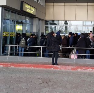Пассажиры стоят у входа в аэропорт Манас, который возобновляет работу после сообщения о взрывном устройстве