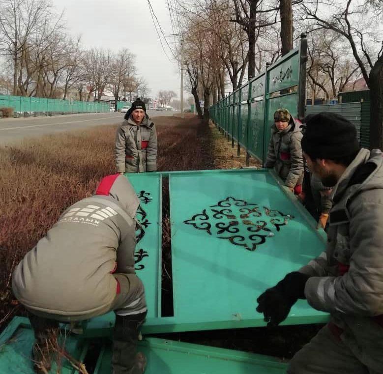 Сотрудники муниципального предприятия Бишкекасфальтсервис демонтируют забор вдоль дороги в Манас в Бишкеке