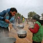 Гуманитарный работник раздает еду в лагере в сирийской провинции Алеппо