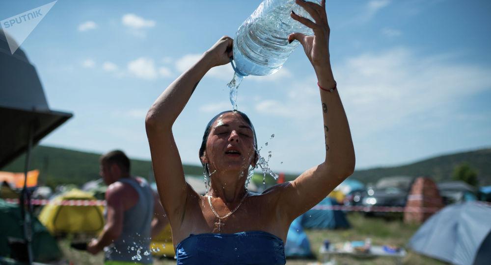 Девушка обливается водой в жаркую погоду. Архивное фото