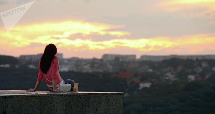 Девушка любуется видом на город. Архивное фото