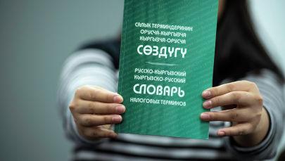 Женщина держит русско-кыргызский словарь налоговых терминов