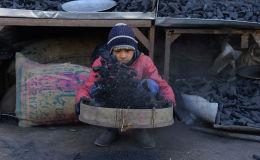 Маленький продавец просеивает уголь в своем киоске в городе Герате