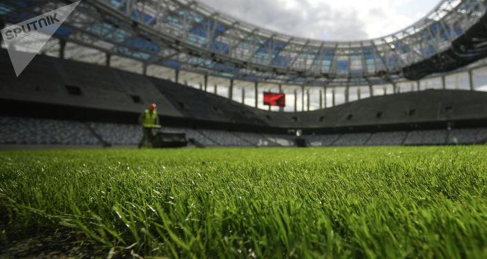 Рабочий стрижет газон на стадионе. Архивное фото