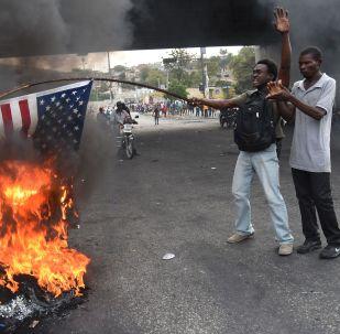 Протестующий сжигает американский флаг во время демонстрации в столице Гаити Порт-о-Пренсе