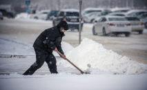 Мужчина убирает снег во время снегопада в Бишкеке. Архивное фото