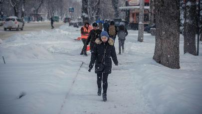 Девушка идет по проспекту Эркиндик во время снегопада в Бишкеке