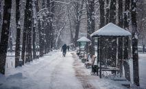 Люди на проспекте Эркиндик во время снегопада в Бишкеке. Архивное фото