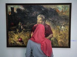 Девушка смотрит на картину на выставке вКыргызском национальном музее изобразительных искусств имени Гапара Айтиева