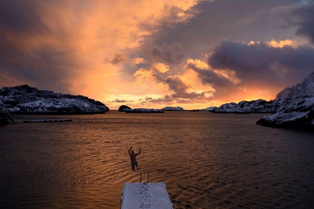 Мужчина прыгает в воду на Лофотенских островах (Норвегия)