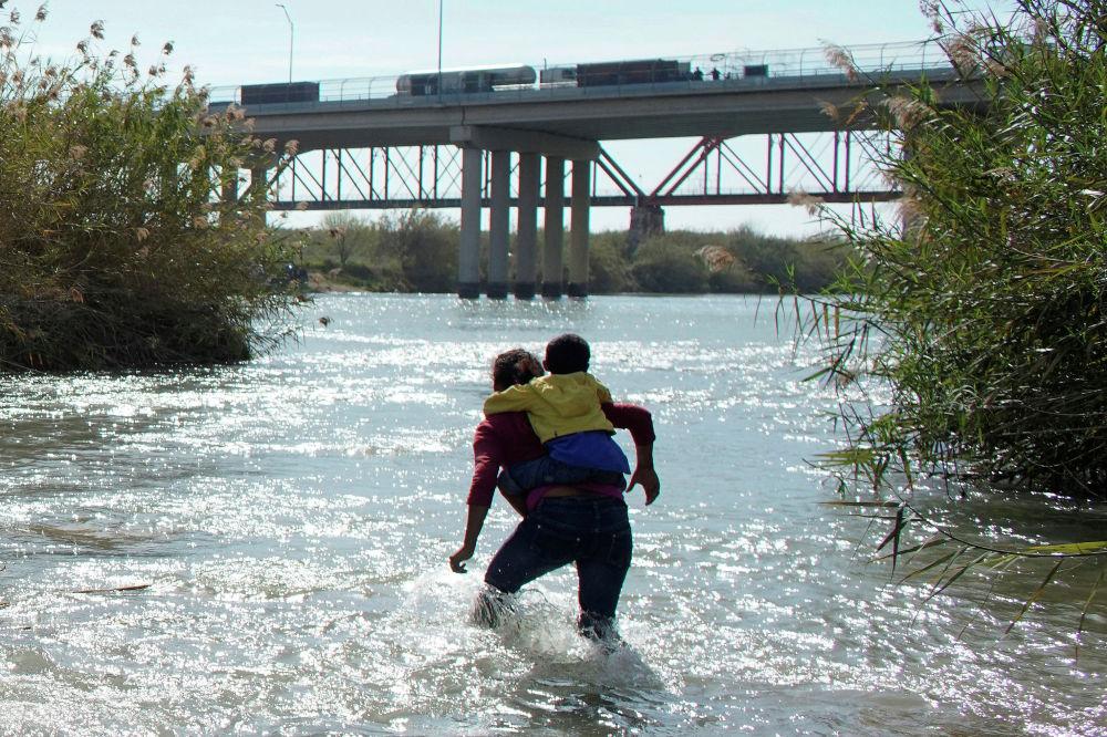 Женщина и ребенок из Гондураса пересекают реку Рио-Гранде на границе Мексики и США. По сообщениям мексиканского МВД, на госрубежах сконцентрировались 5,6 тысячи мигрантов из Гондураса, Гватемалы и Сальвадора, которые хотят попасть в Соединенные Штаты.