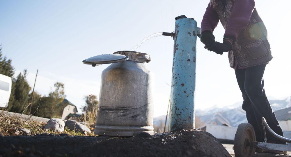 Колонкадан суу алып жаткан айыл тургуну. Архив