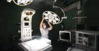 Медицинская сестра регулирует лампу в операционном отделении. Архивное фото