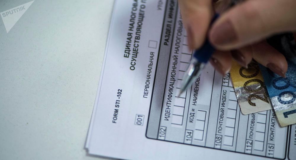 Заполнение документа единой налоговой декларации в КР. Архивное фото