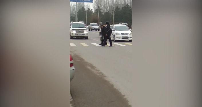 На Южной магистрали инспектор УОБДД увидел пожилую женщину с тростью и помог ей перейти дорогу по пешеходному переходу.