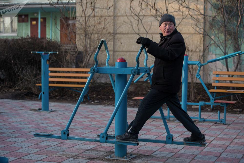 Мужчина делает разминку на тренажере во дворе жилого дома