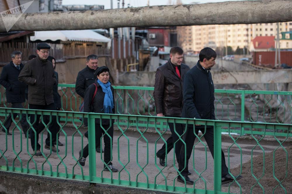 Чиновники проходят по мосту на пересечении улиц Юнусалиева и Сухэ-Батора
