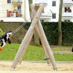 Родители катают своего ребенка на качелях на игровой площадке в Кельне (Германия)