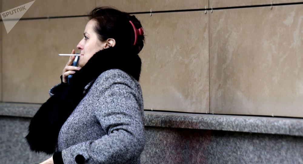 Женщина курит на одной из улиц. Архивное фото