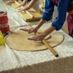 Участница проекта 40 девушек в этнокомплексе Супара раскатывает тесто