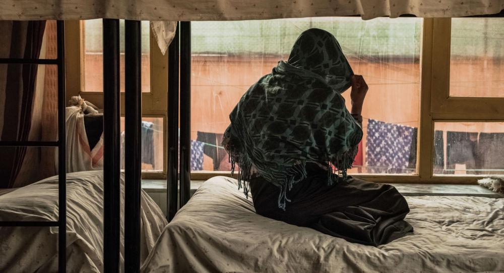 Женщина смотрит в окно своей спальни в приюте для женщин в Кабуле. Архивное фото