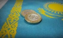Монеты в сто тенге на фоне флага Казахстана. Архивное фото