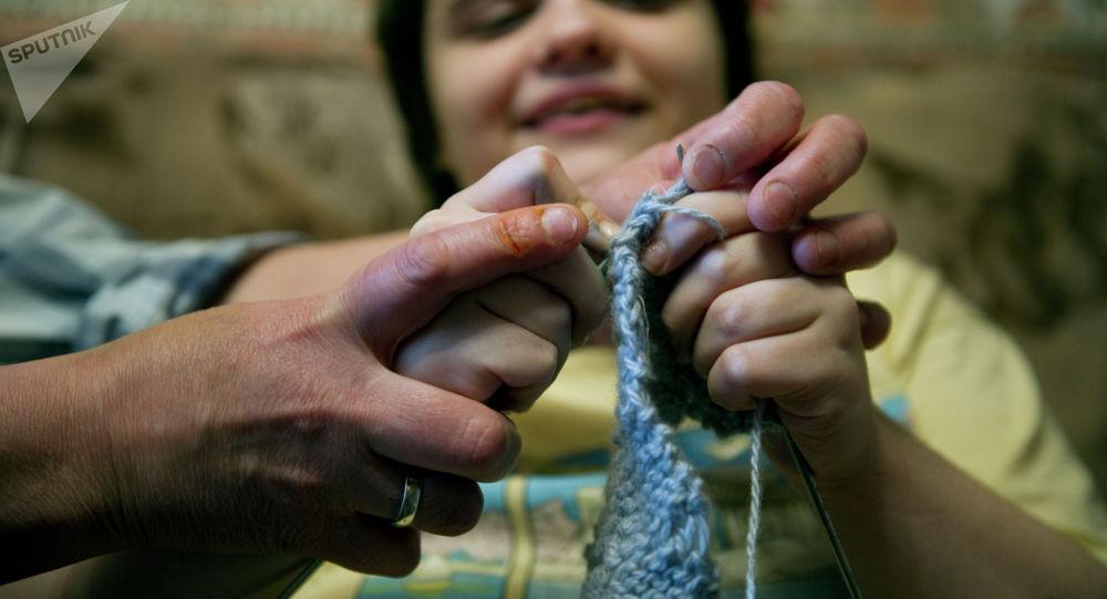 Ребенок с аутизмом учится шить. Архивное фото