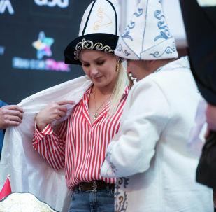 Президент Федерации WEF КР Эмиль Токтогонов помогает одевать чепкен и калпак чемпионке мира по смешанным единоборствам по версии UFC Валентине Шевченко во время встречи с фанатами в Бишкеке