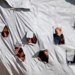 Дети просматривают дыры в палатке в лагере для перемещенных лиц аль-Хол в мухафазе Хасака