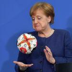 Канцлер Германии Ангела Меркель играет с гандбольным мячом, подаренным ей президентом федерации гандбола Германии (не на снимке), когда она приняла национальную гандбольную команду Германии в канцелярии в Берлине 8 апреля 2019 года