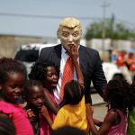 Активист в маске, изображающей Дональда Трампа, в окружении детей возле здания Национального института миграции в Тапачуле. Мексика
