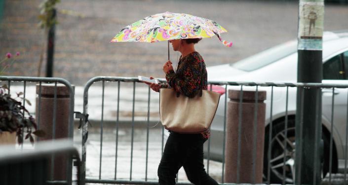 Пешеход пользуется зонтом для укрытия от дождя. Архивное фото