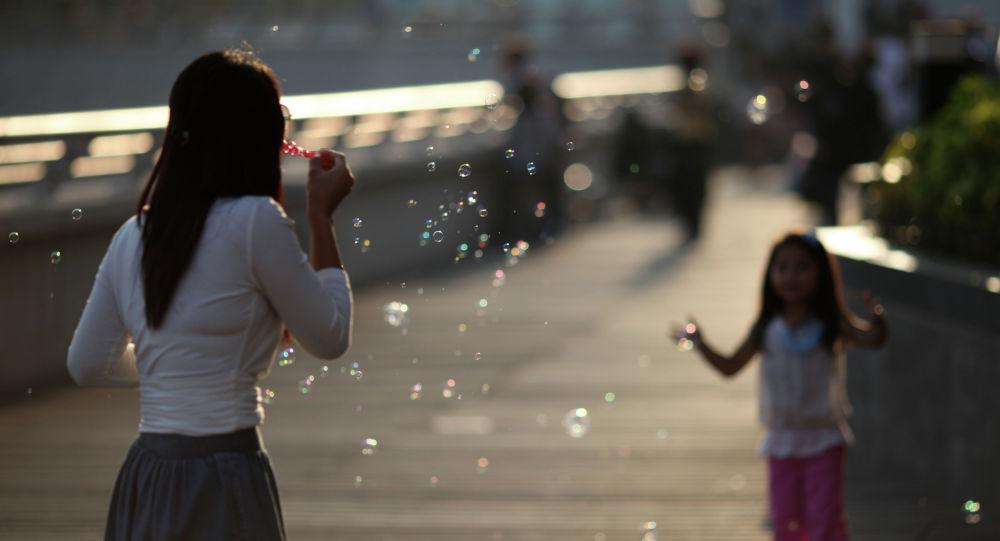 Женщина дует пузыри ребенку. Архивное фото