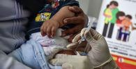 Медицинский работник вводит ребенку вакцину. Архивное фото