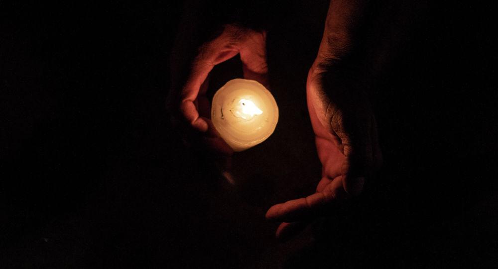 Человек со свечами на руках. Архивное фото