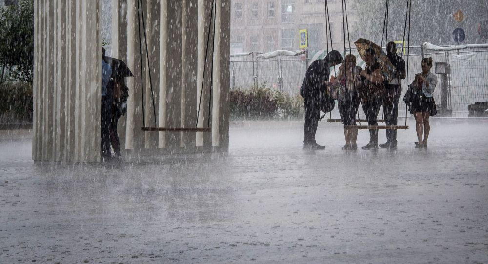 Люди укрываются от проливного дождя. Архивное фото