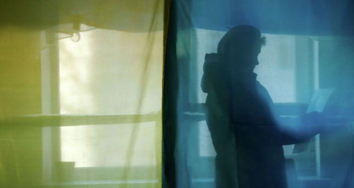 Женщина стоит в кабине для голосования на избирательном участке во время президентских выборов в селе Космач, Ивано-Франковская область, Украина, 31 марта 2019 года.