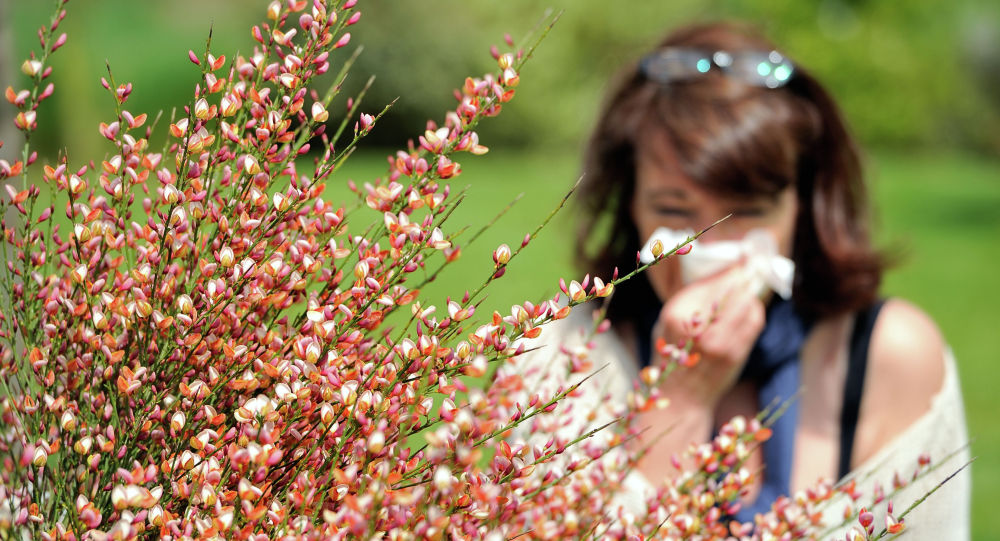 Женщина в парке закрывает платком нос. Архивное фото