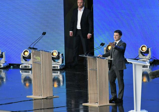 Комик и кандидат в президенты Владимир Зеленский приветствует своих сторонников, когда он прибывает на дебаты со своим соперником, президентом Петром Порошенко, на Олимпийский стадион в Киеве. 19 апреля 2019 года