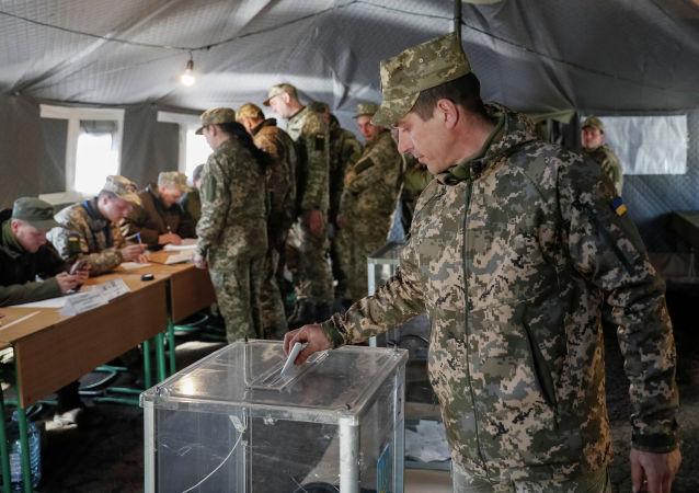 Украинский военнослужащий голосует на втором туре выборов президента на избирательном участке для военнослужащих, в селе Зайцево , Украина, 21 апреля 2019 года