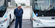 Водитель у нового автобуса из Китая, работающие на газе