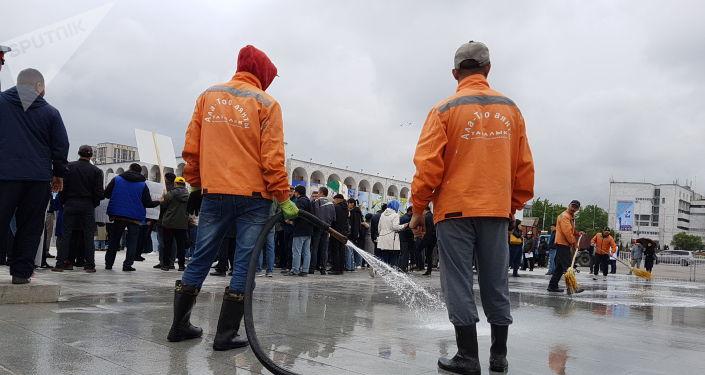 Сотрудники муниципального предприятия Тазалык мыли площадь Ала-Тоо в Бишкеке, несмотря на присутствие митингующих