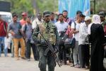 Военнослужащие шри-ланкийской армии стоят на страже на контрольно-пропускном пункте, где они обыскивают людей и их сумки на контрольно-пропускном пункте в Каттанкуди около Баттикалоа. Шри-Ланка, 28 апреля 2019 года