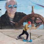 РФ президенти Владимир Путиндин сүрөтү түшүрүлгөн граффитинин жанынан самокат тээп бараткан бала