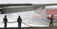Пожарные во время учений по проведению спасательных работ при аварийной посадке воздушного судна. Архивное фото
