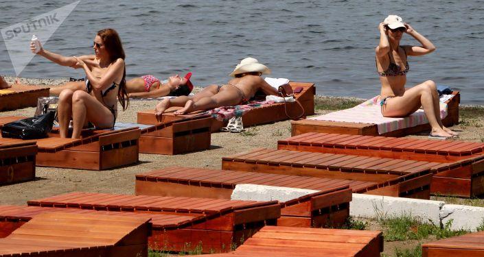 Женщины загарают на шезлонгах на берегу моря. Архивное фото
