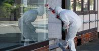 Судебный эксперт в оцепленном доме в Виттингене, северная Германия, где были обнаружены тела трех человек убитых арбалетными болтами. 13 мая 2019 года