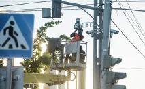Рабочие устанавливают камеру фиксации нарушений ПДД в Бишкеке в рамках проекта Безопасный город. Архивное фото